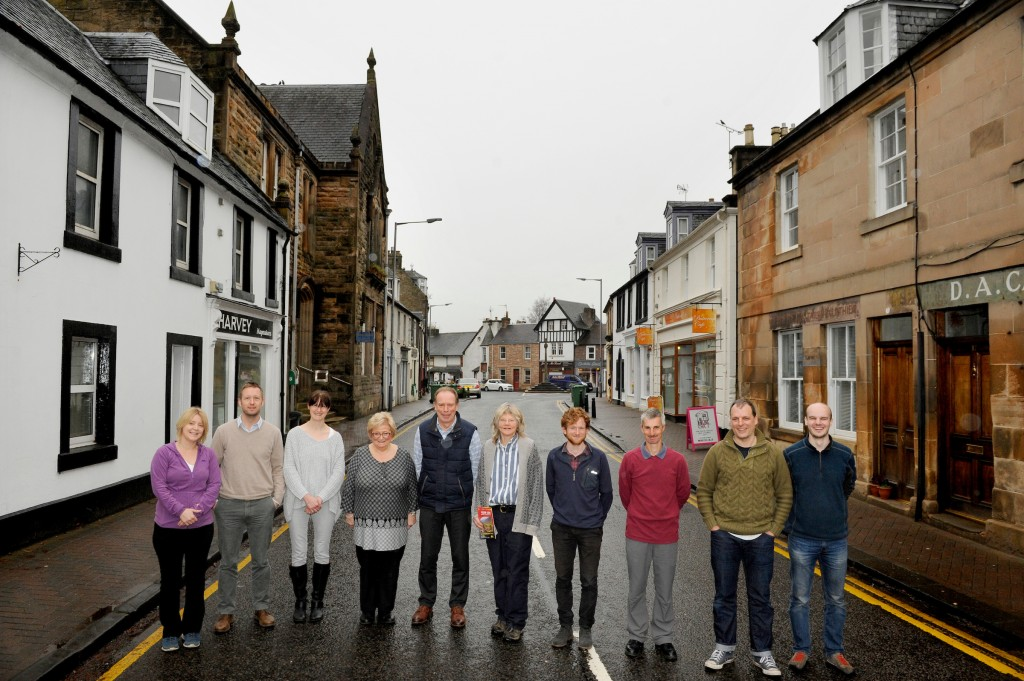 Harvey Maps, Doune, Stirlingshire, 21/11/2017: Harvey Maps staff, with founding directors Robin and Susan Harvey (centre), pictured outside their firm's offices (white building, left) on Doune's Main Street, Stirlingshire.
